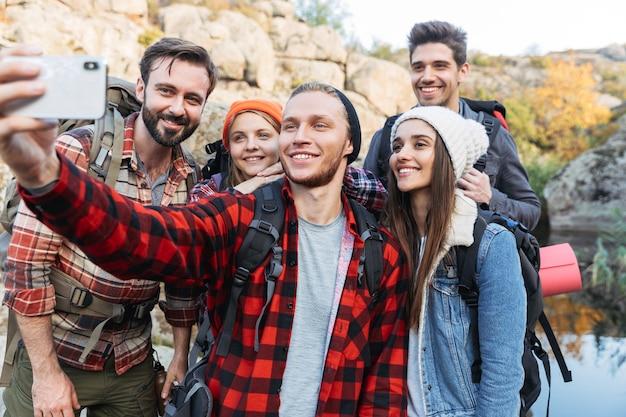 Gruppo di giovani amici felici che trasportano zaini durante un'escursione insieme, facendo un selfie