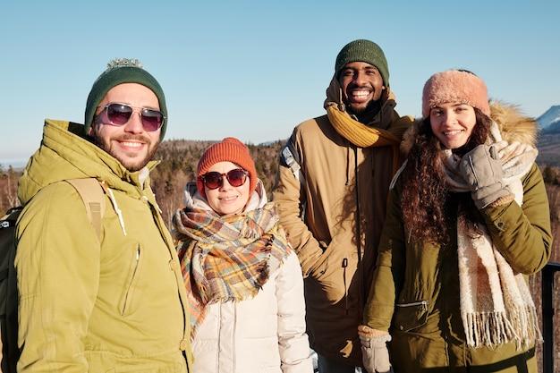 Gruppo di giovani amici felici in abbigliamento invernale in piedi contro il cielo blu
