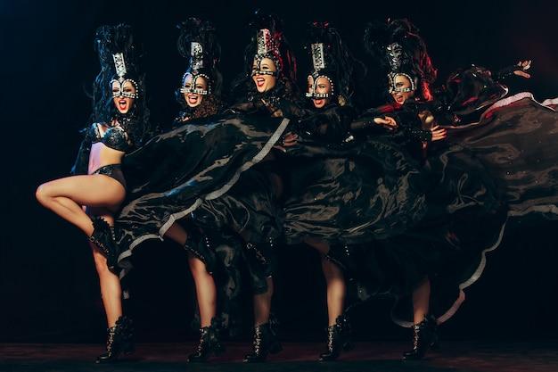 Il gruppo di giovani belle ballerine sorridenti felici con i vestiti di carnevale che posano sul fondo nero dello studio