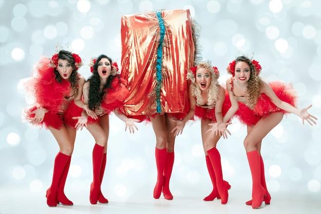 Il gruppo di giovani belle ballerine sorridenti felici con i vestiti di carnevale che posano con il grande regalo sul fondo blu dello studio