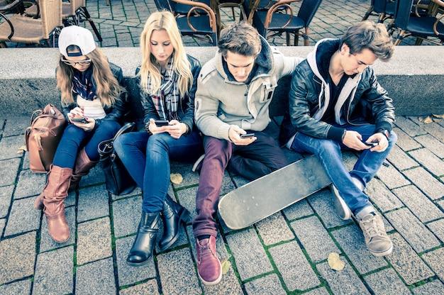 Gruppo di giovani amici hipster che giocano con lo smartphone con reciproco disinteresse l'uno verso l'altro