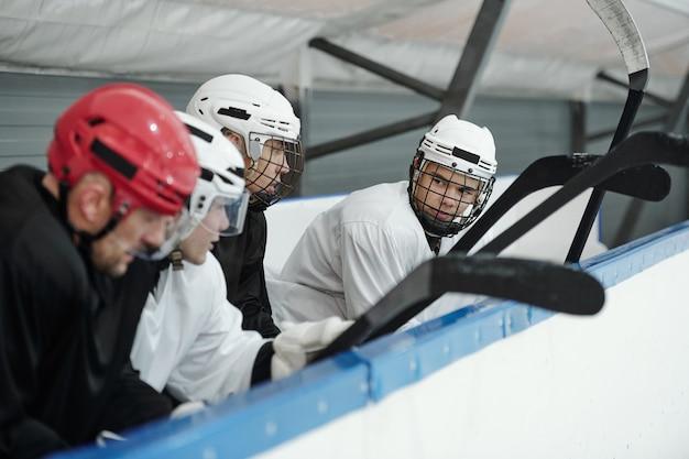 Gruppo di giovani giocatori di hockey in uniforme sportiva e caschi seduti sulla prima fila di tribune dello stadio mentre si preparano per il gioco