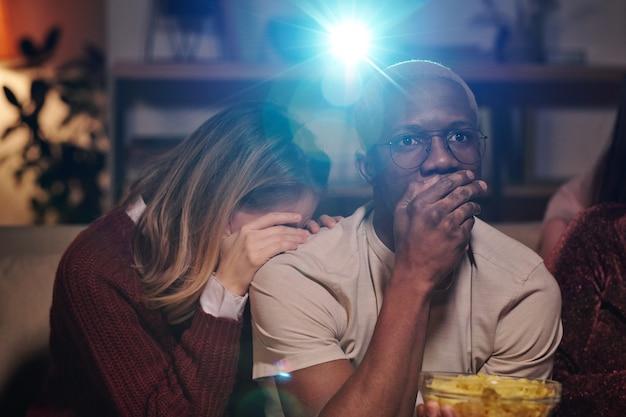 Gruppo di giovani amici interculturali che si rilassano sul divano in soggiorno e guardano insieme film interessanti mentre si godono la festa a casa