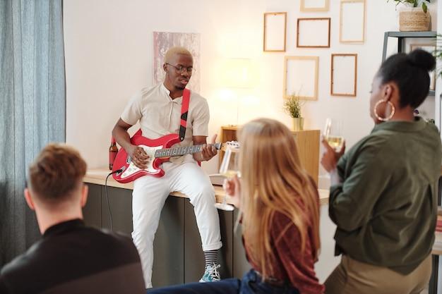 Gruppo di giovani amici interculturali seduti al tavolino con snack e flauto e ascoltando il canto di un ragazzo africano che suona la chitarra alla festa