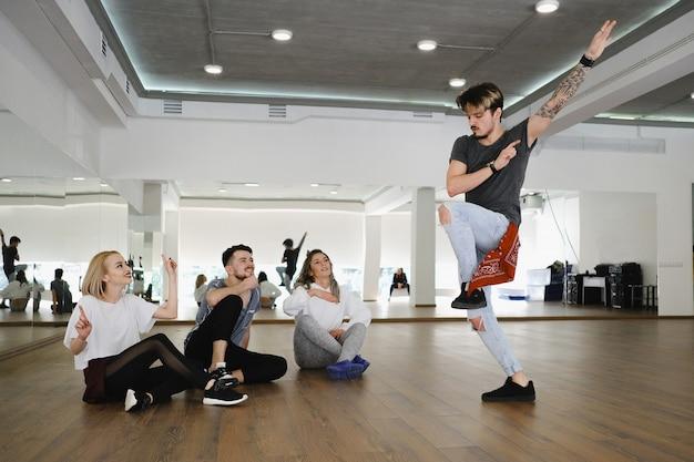 Gruppo di giovani ballerini moderni che ballano nello studio