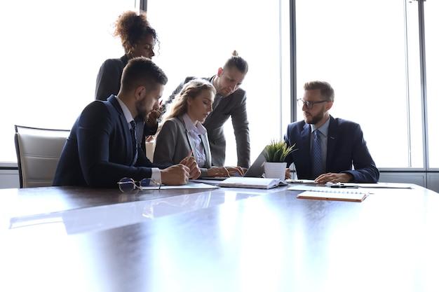 Gruppo di giovani moderni in abiti da cerimonia che discutono di qualcosa mentre lavorano nell'ufficio moderno.