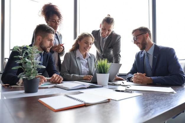 Gruppo di giovani moderni in abiti da cerimonia che sorridono e discutono di qualcosa mentre lavorano nell'ufficio moderno.
