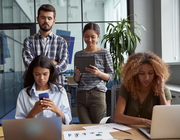 Gruppo di giovani uomini d'affari multiculturali che lavorano insieme in un ufficio moderno utilizzando un tablet portatile