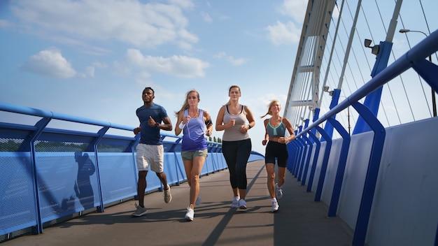 Gruppo di giovani e anziani che corrono all'aperto sul ponte in città.