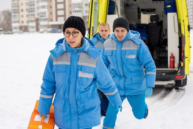 Un gruppo di giovani paramedici in uniforme blu che esce dall'auto dell'ambulanza e che si affretta a persona malata all'aperto in inverno