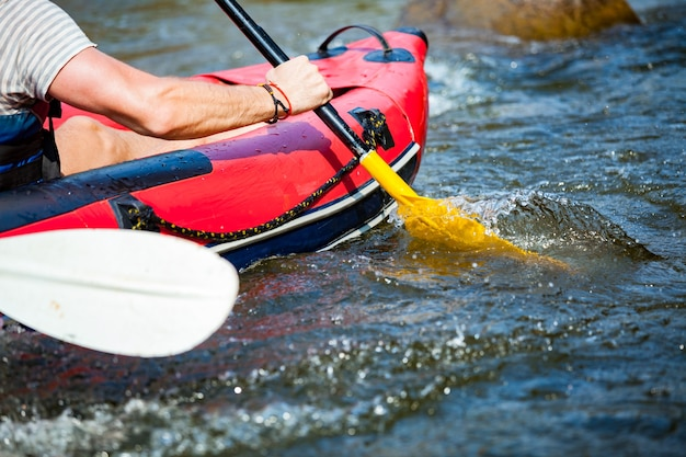 Il gruppo di giovani sta trasportando rafting in un fiume. avvicinamento