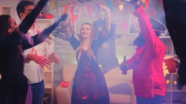 Gruppo di giovani vestiti con abiti diversi per la festa di halloween ballando e divertendosi