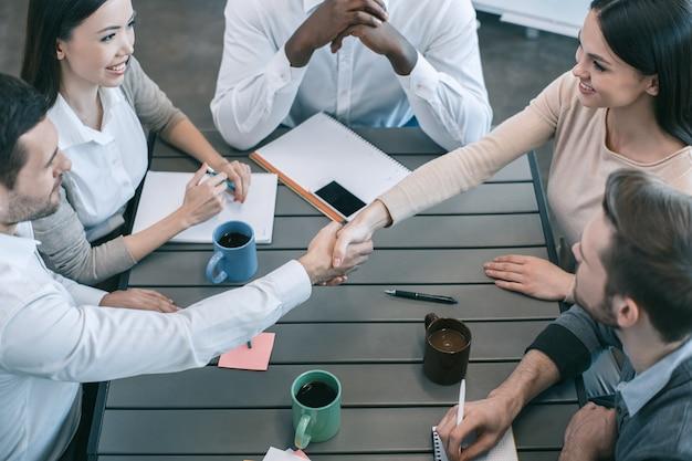 Un gruppo di giovani che hanno una riunione d'affari lavora insieme