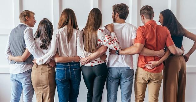 Gruppo di giovani che abbracciano insieme vista posteriore.