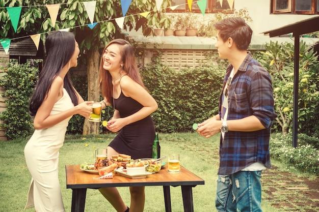 Il gruppo di giovani fa festa felice mentre gode della festa a casa sulla casa del giardino