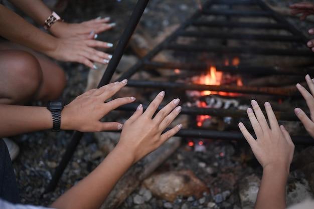 Gruppo di giovani che si rilassano e si godono la serata estiva intorno al fuoco.