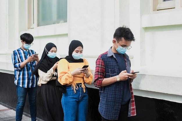 Gruppo di giovani in fila che tengono le distanze sociali contro la diffusione del coronavirus