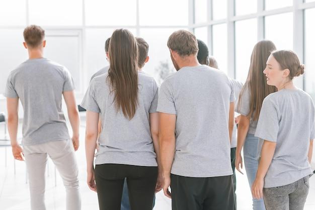 Un gruppo di giovani in piedi in una stanza luminosa
