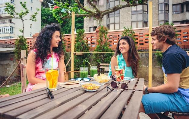 Gruppo di giovani che parlano e ridono intorno al tavolo con bevande salutari in una giornata estiva di svago all'aperto