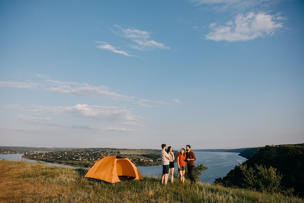 Gruppo di giovani accanto a una tenda in montagna con vista sul fiume.