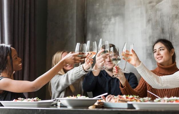 Gruppo di giovani che tostano i bicchieri di vino