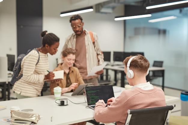 Gruppo di giovani che utilizzano computer nella biblioteca scolastica, concentrarsi sul giovane che scrive codice in primo piano, copia spazio