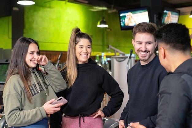 Gruppo di giovani che utilizzano e che guardano insieme il telefono cellulare.