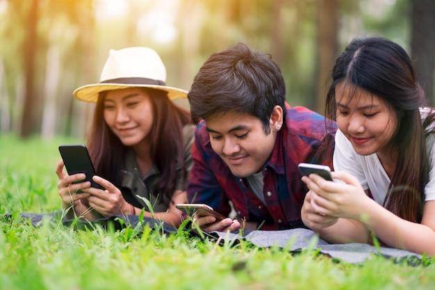 Un gruppo di giovani che usano il cellulare mentre sono sdraiati nel parco