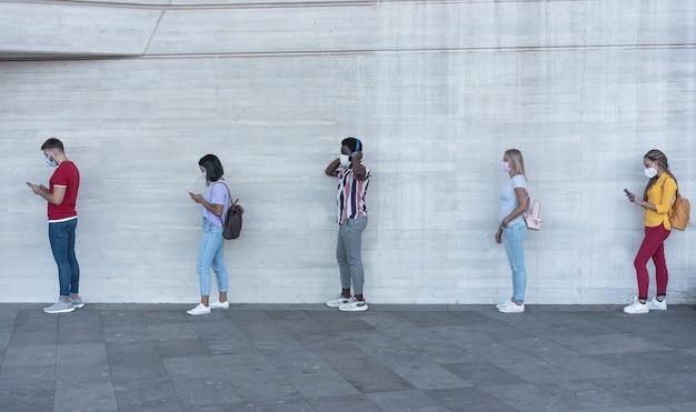 Gruppo di giovani in attesa di entrare nel mercato di un negozio mantenendo la distanza sociale in linea durante il tempo di coronavirus