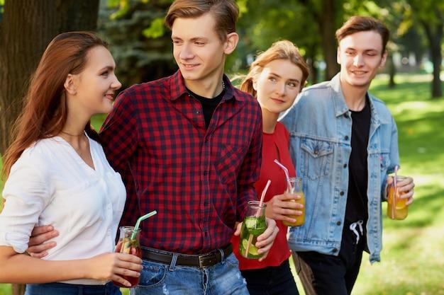 Un gruppo di giovani con cocktail detox trascorrono del tempo insieme in estate