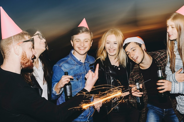 Gruppo di giovani con stelle filanti e alcol che parlano tra loro mentre si trovava nella natura di notte