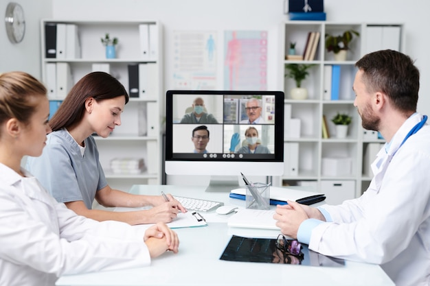 Gruppo di giovani professionisti che si consultano con i colleghi durante la comunicazione online mentre sono seduti davanti al monitor del computer in uno studio medico