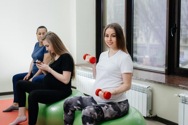 Un gruppo di giovani madri incinte è impegnata in pilates e sport con la palla in un fitness club. incinta