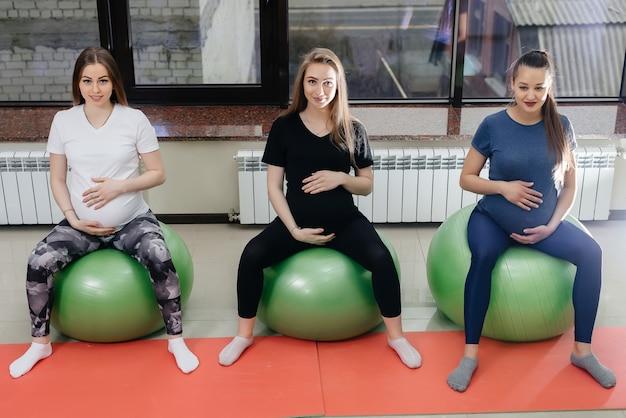 Un gruppo di giovani madri incinte è impegnata in pilates e sport con la palla in un fitness club. incinta.