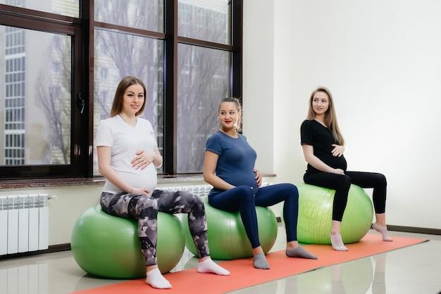 Un gruppo di giovani madri incinte è impegnata in pilates e sport con la palla in un fitness club.