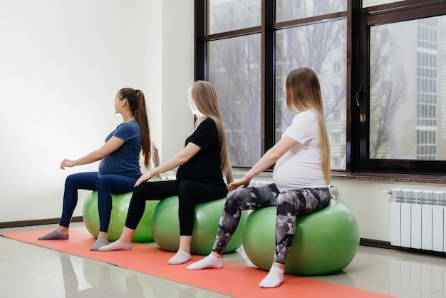 Un gruppo di giovani madri incinte è impegnato in pilates e sport con la palla nel fitness club.