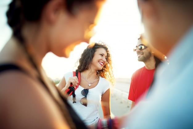 Gruppo di giovani amici sorridenti con occhiali da sole e zaini.