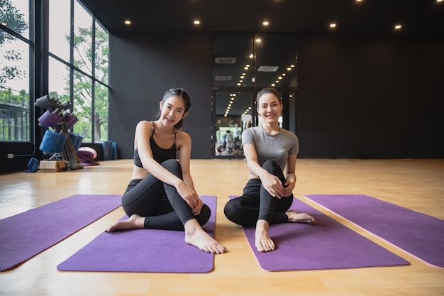 Il gruppo di giovani donne asiatiche sportive si siede sulle stuoie di yoga che sorride e che parla dopo la pratica dell'yoga