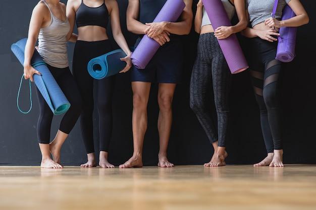 Gruppo di giovani sportivi e donne con tappetini da yoga in piedi al muro nero che parlano dopo l'esercizio