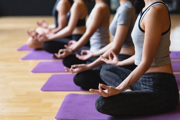 Il gruppo di giovani sportivi che praticano la classe di yoga che fa la posa del loto di meditazione con lo spazio della copia, lo yoga e la forma fisica risolvono lo stile di vita di sanità nel club di forma fisica
