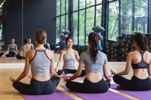 Il gruppo di giovani sportivi che praticano la classe di yoga che fa il loto di meditazione posa con lo spazio della copia