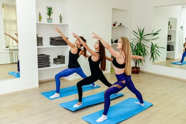 Gruppo di giovani sportivi che praticano la lezione di yoga con istruttore, allungando nell'esercizio del bambino,
