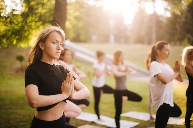 Un gruppo di giovani donne sportive sta praticando una lezione di yoga in piedi nell'esercizio vrksasana. le ragazze sono in equilibrio su un tappetino da yoga su una gamba all'alba sulla posa dell'albero con gesto namaste