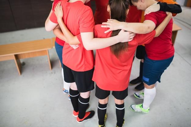 Gruppo di giovani donne sportive in abbigliamento sportivo in piedi in cerchio, abbracciando e pregando prima della partita in spogliatoio
