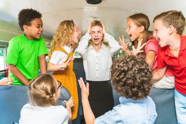 Gruppo di giovani studenti che frequentano la scuola primaria su uno scuolabus giallo - bambini delle scuole elementari che si divertono