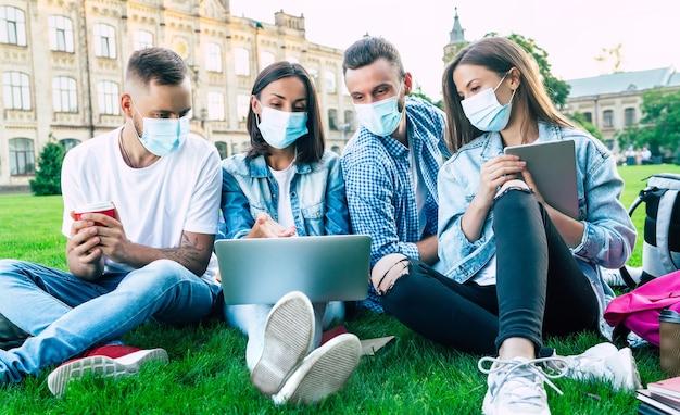 Un gruppo di giovani studenti in maschere mediche con laptop e libri stanno studiando insieme all'università. amici all'aperto seduti sull'erba.