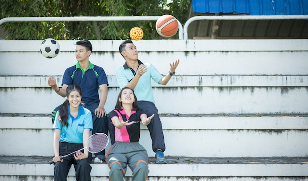 Gruppo di giovani studenti svolgono sport sull'anfiteatro, concetto sano