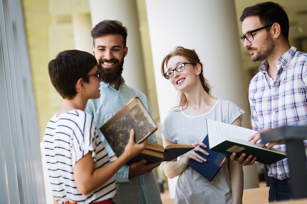 Gruppo di giovani studenti che studiano insieme in biblioteca