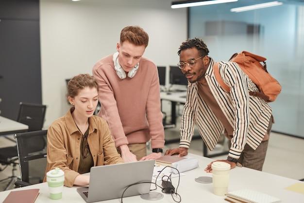 Gruppo di giovani studenti che usano il laptop insieme mentre lavorano a un progetto scolastico in un college moderno, copia spazio