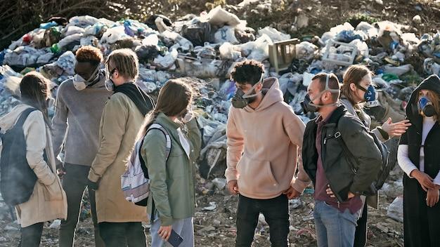 Un gruppo di giovani volontari in maschera antigas si prende cura dell'ambiente mentre si trova in discarica di immondizia...